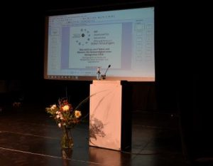 kurz vor Beginn der Tagung: Podium und Blumenstrauß, Logo und Titel auf der Leinwand